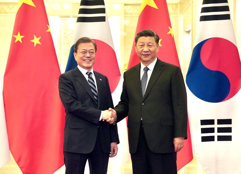 12月23日,韩国总统文在寅和中国国家主席习近平在北京人民大会堂举行首脑会晤前握手致意。图片来源:韩联社